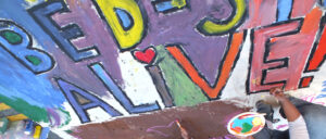 "The detail from the ""Alive"" artwork seen here was conceived by Bernice E. Green for the October 2011 ""Bed-Stuy Alive"" event and designed by artist/photographer and Horace Mann art teacher Barry L. Mason who led Bed-Stuy residents of all ages in the open-air Fulton Street communal mural painting project. Several community, business and political leaders, including Councilman Al Vann and Assemblywoman Annette Robinson, also participated in the project during which Project Green certificates were distributed to all who lifted a brush. Photo credit: Matthew Frasier."