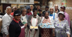 Faith-stirrers: Bridge Street boasts a Free Food program, where all the supporters, unpaid, cook and clothe those in need, from the heart. They include, from left to right: Delores Canty, Carrie Barfield, Beatrice Shavers, Carol Nether, Helen Jefferson, Juliette Thornhill,  Charleen Croom, Elizabeth Ferdinand (background), Helen Jones, Earl Batts, Patricia Mitchell, Phyllis Johnson, Colin Johnson,Priscilla Sedney and, far right, Irene Evans.   Retired Medgar Evers College educator Dr. James Barnes, a pianist (unpictured), awho plays music for the staff's devotional every Wednesday preceding each meal, was on his way.   (Photo credit: Bernice Green)