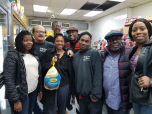 "Brooklyn leader Edolphus (""Ed"") Towns, now considered a political statesman emeritus, assisted by Nikki Lucas, Democratic District Leader of the 60th Assembly District, helped Modern Meats market owner Arti Molineli and his staff distribute 600 turkeys to regular customers and other East New York families on Saturday, November 19. The giveaway called our attention to Uptown Brooklyn East as a small-business nexus and a major attraction for larger enterprises seeking to fulfill corporatecommunity partnership missions: family-owned Modern Meats celebrates its 70th year at the location, next year; the event was fully sponsored by Mr. Arker.(Photo credit: Juanita James)"